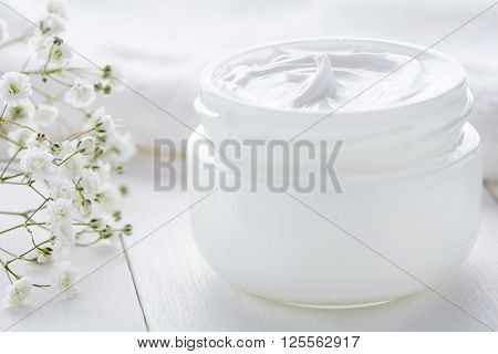 Dermatology cosmetic cream with flowers hygienic skincare product in glass jar on white background