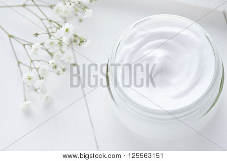 Hygienic cream bodycare product wellness and relaxation makeup mask in glass jar with towel on white background