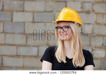 Young architect with yellow helmet near his workplace