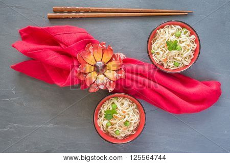 Overhaead view of bowls of asian noodles in a vegetable broth.