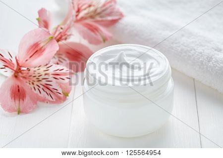 Natural facial cream dermatology cosmetic product wellness and relaxation makeup mask in glass jar with towel on white background