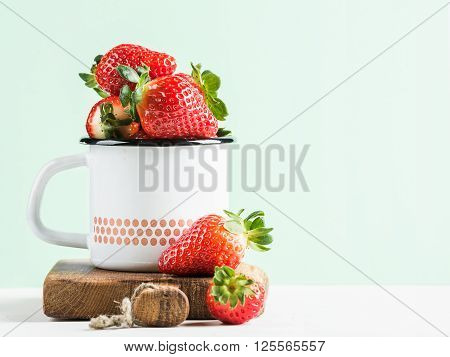 Fresh ripe red strawberries in country style enamel mug on rustic wooden board, pastel light mint background, selective focus, copy space