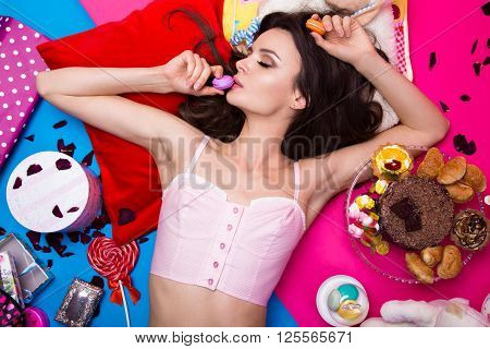 Beautiful fresh girl doll lying on bright backgrounds surrounded by sweets, cosmetics and gifts. Fashion beauty style. Photos shot in the studio.