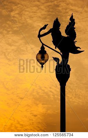 Silhouette Thai art statue lamppost in the evening.