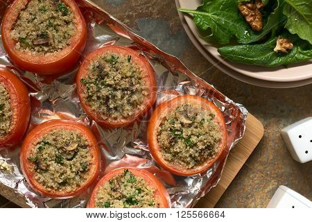 Vegetarian baked tomato stuffed with quinoa mushroom and parsley with spinach and walnut salad on the side photographed overhead on slate with natural light