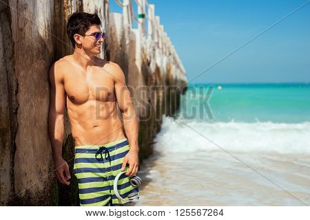 Handsome and sexy man walking on the beach.