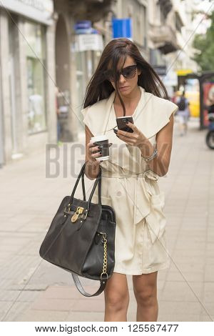 Stylish young business woman wearing short white dress and sunglasses texts in urban setting while holding coffee and bag