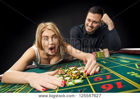 Couple playing roulette wins at the casino, gambling chips taken by hands woman