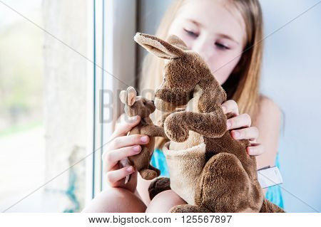 beautiful girl 8 years old playing with her toy big and little kangaroos near window