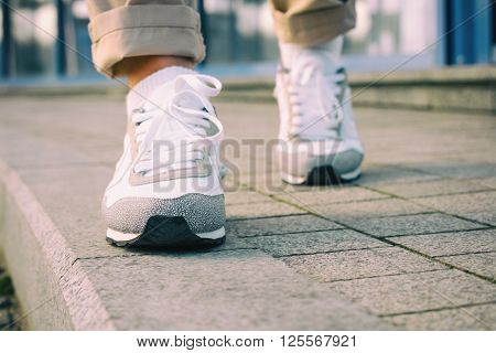 Female feet in white sneakers walking on the sidewalk low angle retro colors.