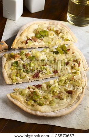 Homemade leek and bacon tarte flambee a traditional French and German oven baked pizza-like pie photographed on parchment paper with natural light (Selective Focus Focus on the front of the middle slice)