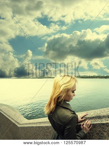 Pensive woman leaning on granite sea-wall ander sky with clouds, toned image, profile view
