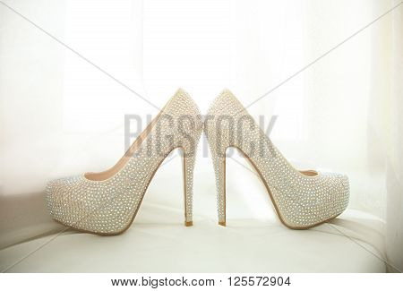 Elegant bridal white shoes with rhinestones closeup.