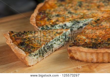 pie with cottage cheese, herbs and cheese with cut pieces on a wooden board ** Note: Shallow depth of field