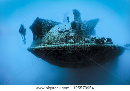 Scuba diver exploring the stern section of a shipwreck.
