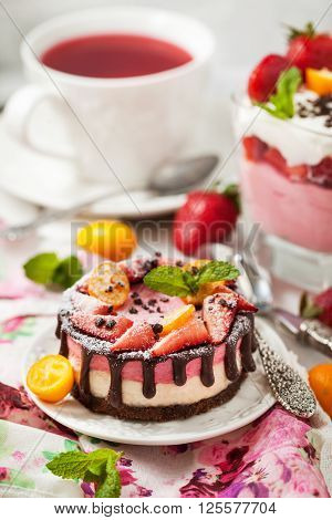 Delicious individual mini cake (cheesecake) decorated with chocolate and strawberry
