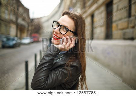 Businesswoman on cellphone walking down the street while talking on smart phone. Happy smiling caucasian business woman busy