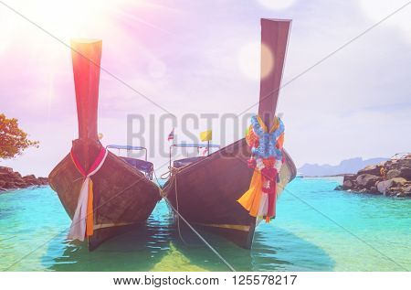 boats, sea and cliffs with lens flare at koh Phi-Phi, Thailand