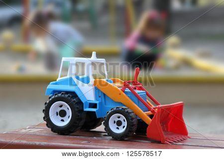 children's toy - the car bulldozer. indistinct background
