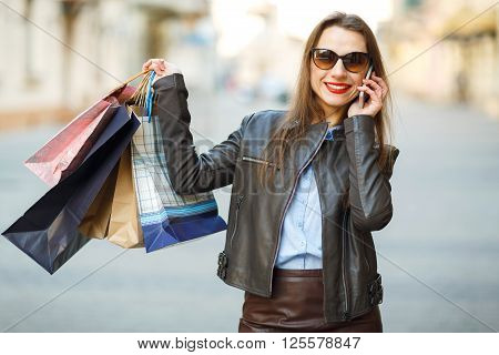 Sale shopping tourism and happy people concept - beautiful woman with shopping bags is talking on smart phone on a street