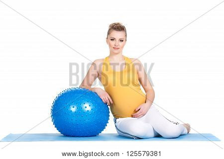 The young pregnant woman, the blonde with brown eyes, is dressed in a yellow jersey and white sports pants, carries out a set of exercises for pregnant women with a big gymnastic ball of blue color in studio on a white background