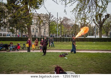 STRASBOURG FRANCE - APR 9 2016: Fire-eater performing as people join the 'Nuit Debout' or 'Standing night' movement at the Place de la Republique in Strasbourg