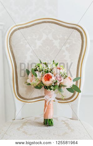 Wedding bouquet on chair. Bride's traditional symbolic accessory. Floral composition with peonies and roses.