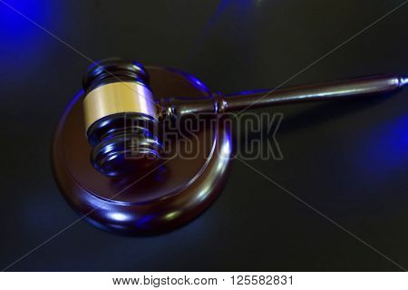 Judge's court gavel with blue police lights