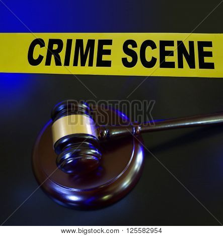 Court gavel and crime scene tape with blue police lights