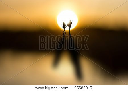 Young couple holding hands back lit by sun at dawn casting long shadows