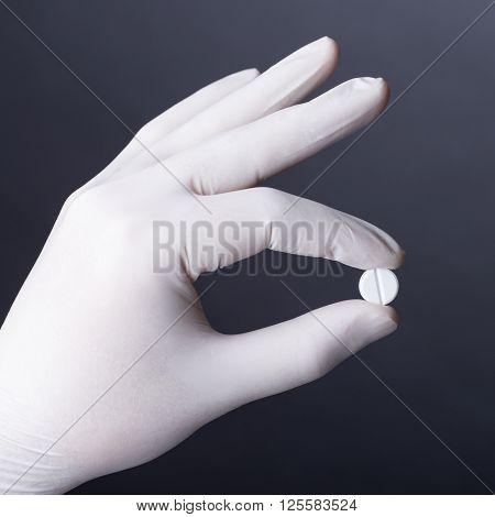 Hand in white latex glove holding white pill on dark background