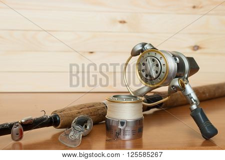 a fishing rod and reel on a wooden background
