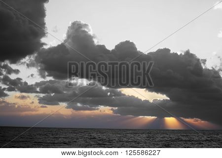 selective desaturation of a dramatic sky over the sea at sunset
