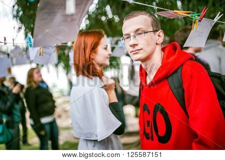 Omsk, Russia - May 21, 2014: Festival of Photography in street, people watching, a man in a red hoodie