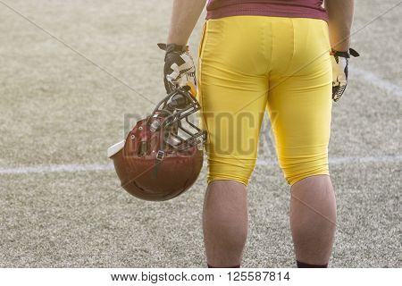 Player in red and yellow jersey holding sport helmet on the football field