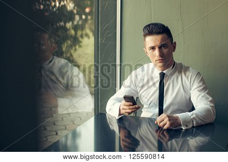 Man young handsome elegant model wears white shirt black skinny necktie with smart phone sits at table reflects in glass window and looks in camera indoor on grey background
