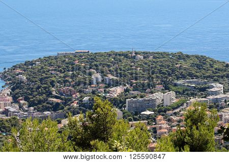 Monte Carlo Monaco - September 20 2015: peninsula with densely populated town and green trees on sea coast view from mountain on seascape background