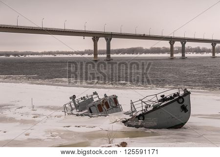 Vessel wreck in a frozen river covered with ice