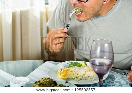 Man sitting by classy dinner setting eating fork with broccoli, crepe covered in white sauce lying on plate.