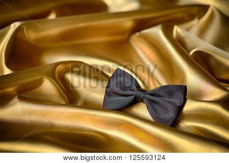 Black bow tie on draped golden satin