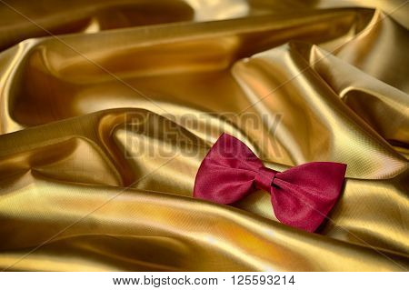 Red bow tie on draped golden satin
