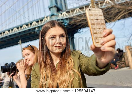 NEW-YORK - CIRCA MARCH 2016: woman taking a selfie in New-York. A selfie is a self-portrait photograph, typically taken with a camera phone held in the hand or supported by a selfie stick.