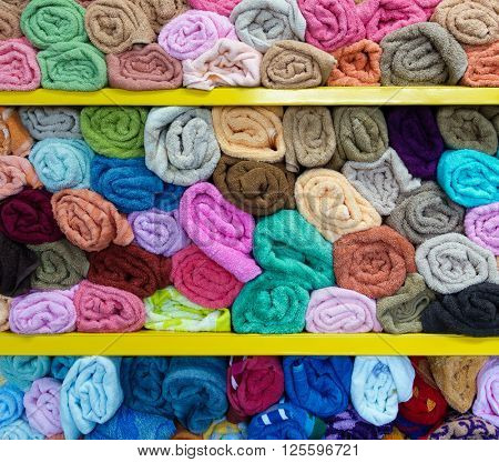 Colorful rolled towels on shelves in a shop