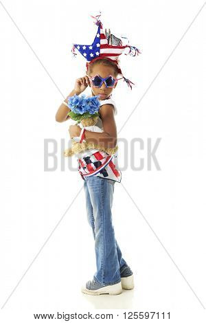 A young elementary girl ready to tip her glasses in her self-created American patriotic outfit.  On a white background.