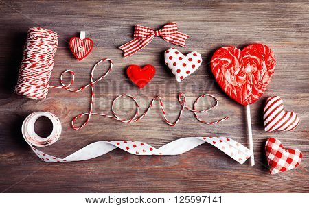 Valentine concept. Inscription Love with hearts and candy on wooden table background