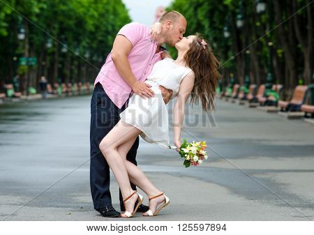 First kiss. Young couple of lovers in love passionately kissing standing on path in summer park. Full body portrait of male and female loving and hugging each other.