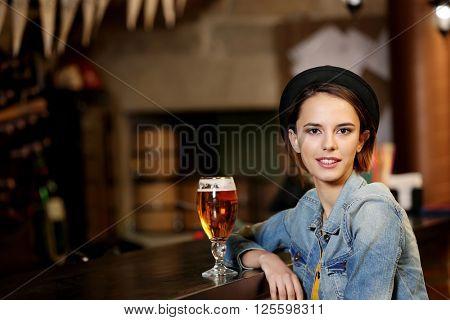 Young woman drinking beer in a bar