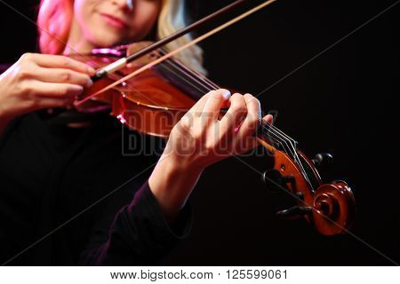 Woman plays violin on black background, close up