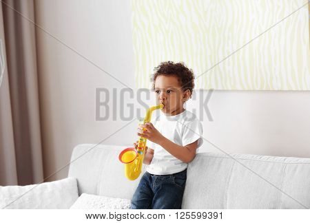 Little boy playing  with musical toy on the couch