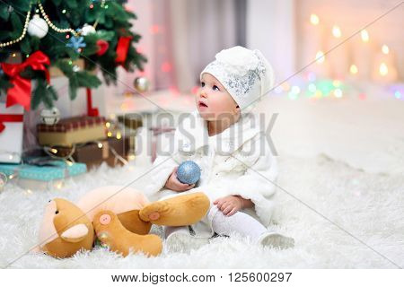 Funny baby girl with Christmas toy near  Christmas tree on bright background